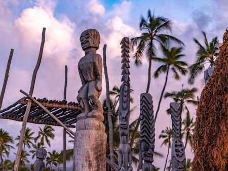 Wood carving at a Hawaiian temple glow in the setting sun