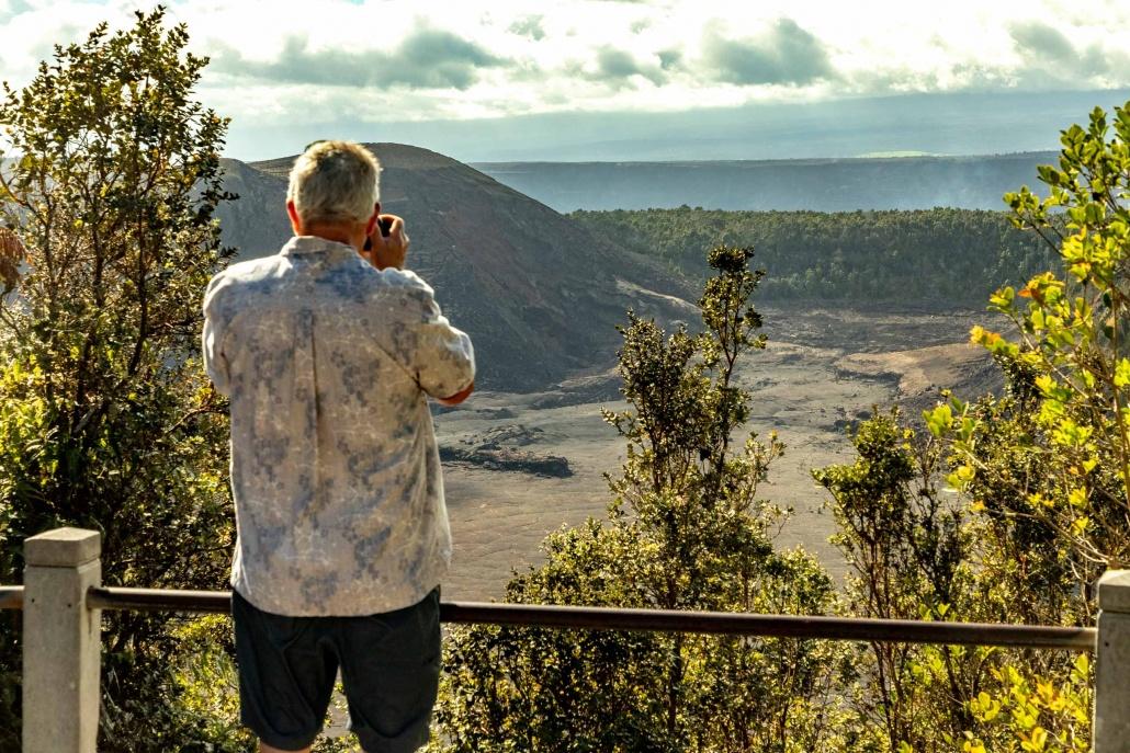 A visitor stands at an overlook of a Hawaiian volcanic caldera
