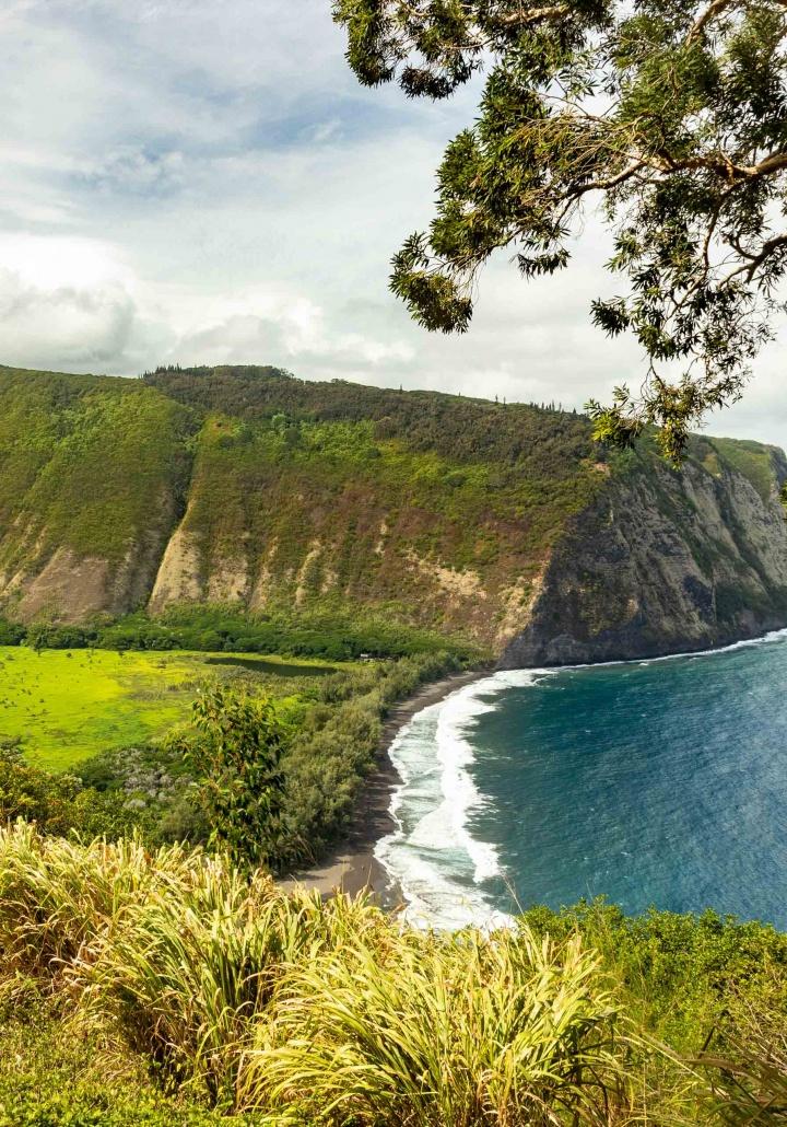 Valley cliffs nearly a thousand feet above a black sand beach
